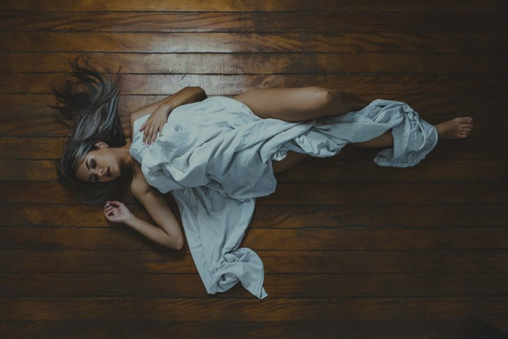 Pose com lençol em sessão de ensaio sensual feminino feito em estúdio